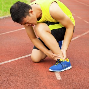 young male runner with ankle injury on track in the stadium