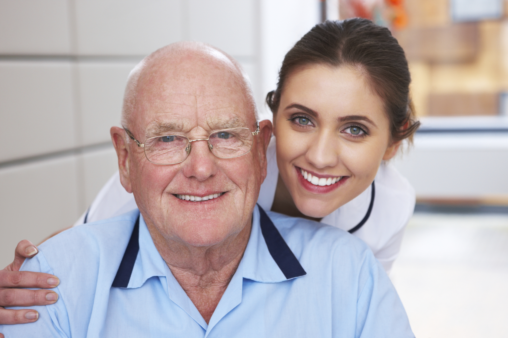 Attractive nurse and her elderly patient smile together for the camera. Horizontal shot.
